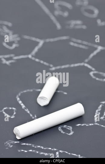 Two pieces of chalk on chalkboard with chemical formula - Stock-Bilder