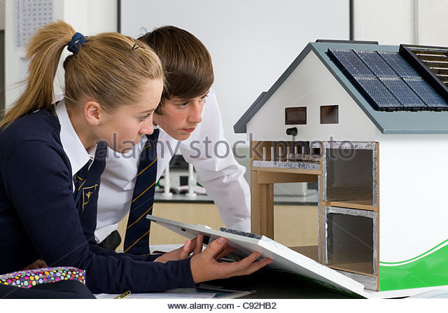 Students in school uniforms examining energy efficient house model in science class - Stock Image