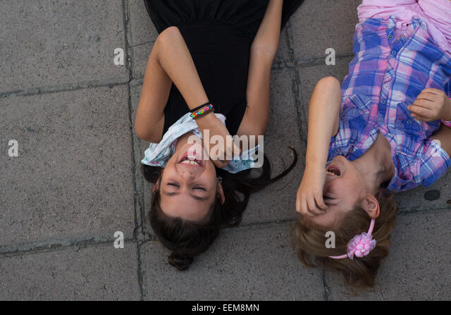 Two girls lying on ground laughing - Stock Image