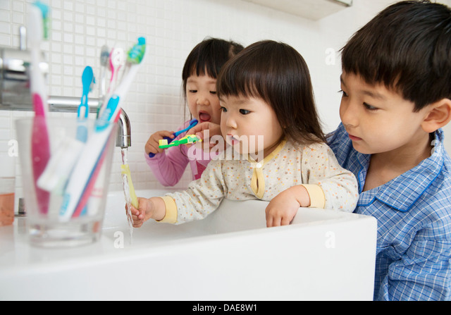 Brother helping sisters to clean teeth - Stock Image