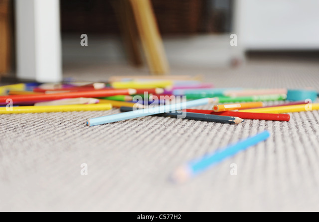 Colored pencils in pile on floor - Stock Image