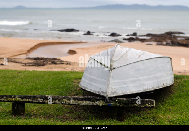 An old dingy boat on the beach. - Stock Image