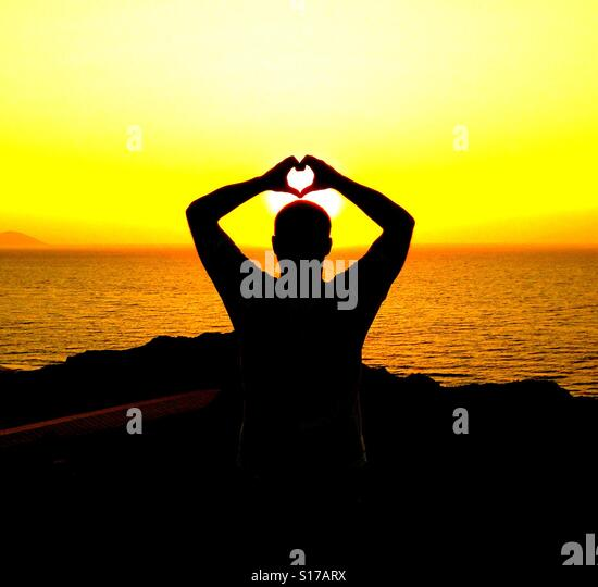 Silhouette of a man forming a heart shape with his hands - Stock-Bilder