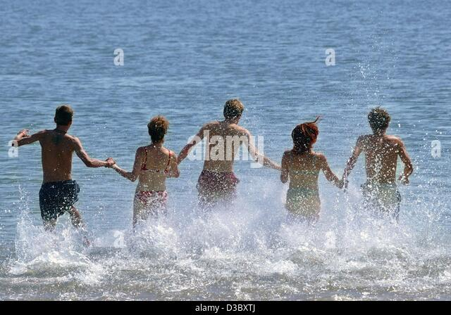 (dpa) - Holidaymakers run into the 23 degree Centigrade warm North Sea on a beach on the island Amrum, Germany, - Stock Image