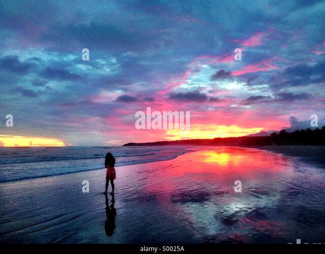 Woman walking on beach. Las Flores, El Salvador. Sunset. - Stock Image