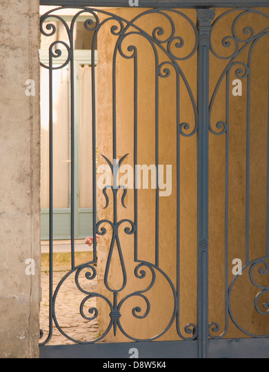 Part on an old ornate iron gate to a courtyard, Arles, France - Stock Image