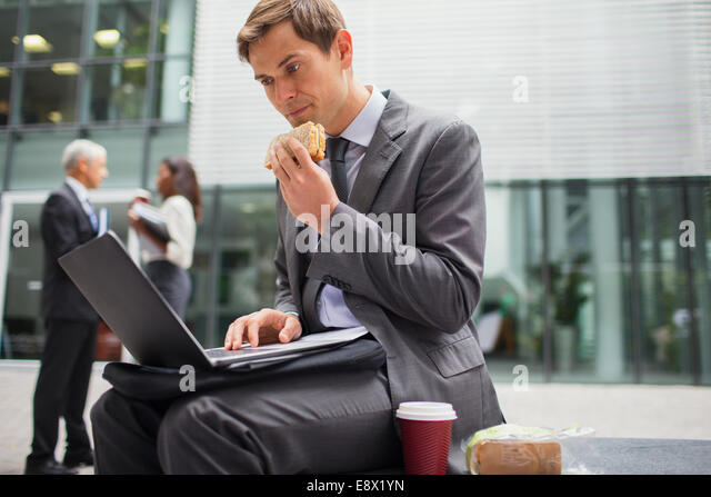 Businessman eating lunch while working outside office building - Stock Image