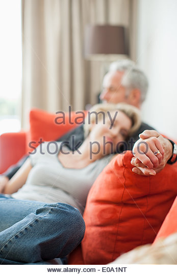 Mature couple laying on sofa holding hands - Stock-Bilder