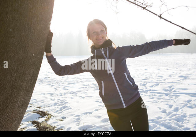 Young woman stretching in winter landscape - Stock Image