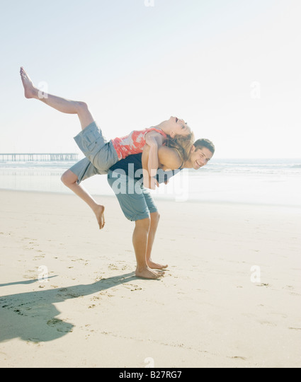Couple playing around on beach - Stock-Bilder