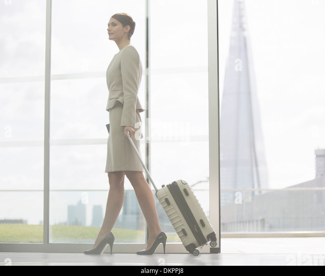 Businesswoman rolling suitcase in airport - Stock Image