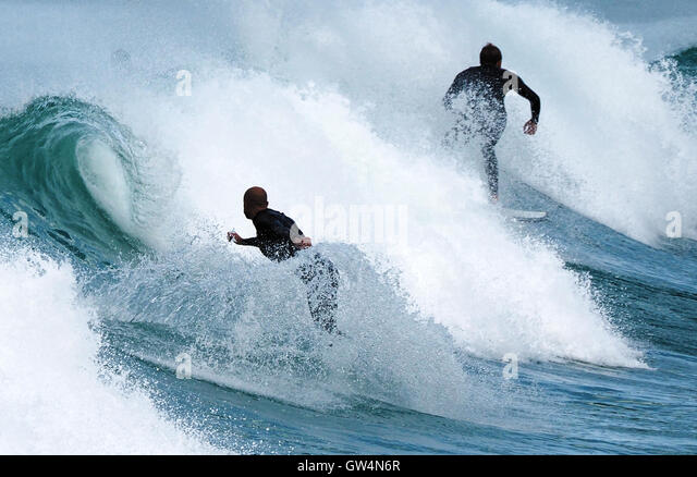 Two black wetsuit male surfers surf dramatic curling Fistral beach breaking waves - Stock Image