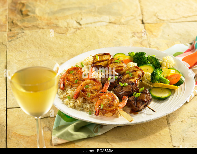 Shrimp, beef and chicken skewers with mixed vegetable on rice - Stock Image