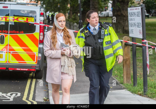 London, UK. 15th Sep, 2017. A bandaged woman is escorted by a Police Officer from Parsons Green underground station - Stock Image