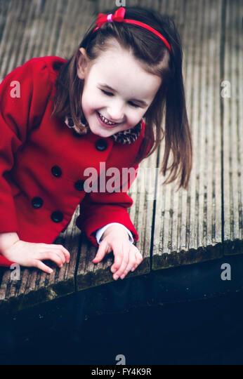 a small girl sitting on wood alone and smile - Stock Image