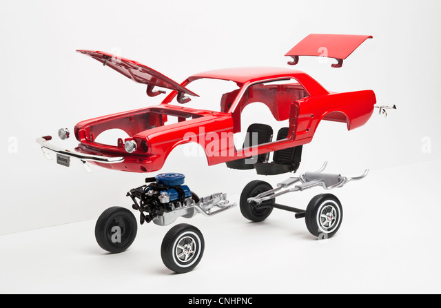 A model car taking a part, some pieces in mid-air - Stock Image
