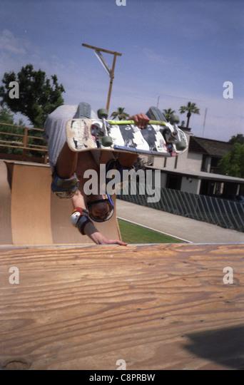 Skateboarding session in Visalia, California in October 1987. half pipe vert vertical hand plant - Stock Image