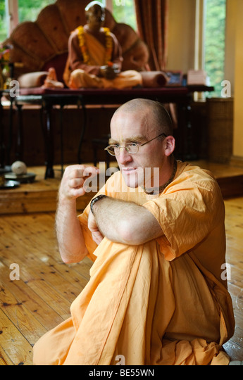 Hare Krishna disciple in a temple room, with statue of His Divine Grace A.C. Bhaktivedanta Swami Prabhupada behind. - Stock Image
