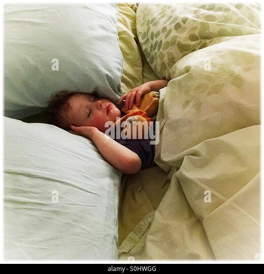 Toddler sleeping in a big bed - Stock Image