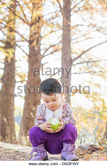 Child with green apple in deep thought - Stock Image