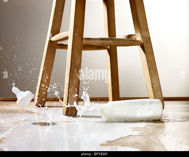 baby bottle and spilled milk with splash on a floor - Stock Image