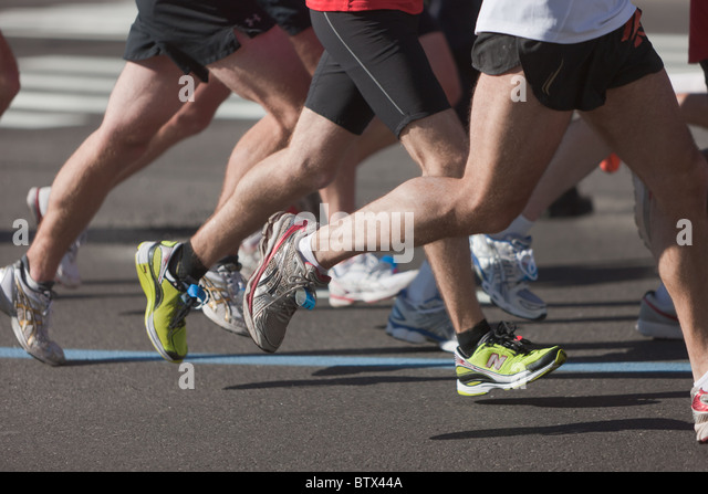 The legs and feet of runners during the 2010 New York City Marathon. - Stock Image