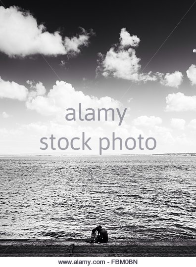 Couple Sitting At Seaside Against Cloudy Sky - Stock-Bilder