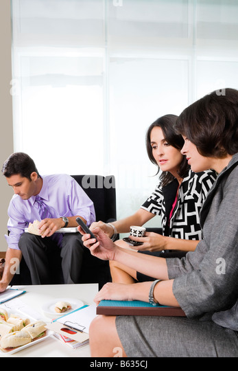 Two businesswomen looking at a mobile phone - Stock Image