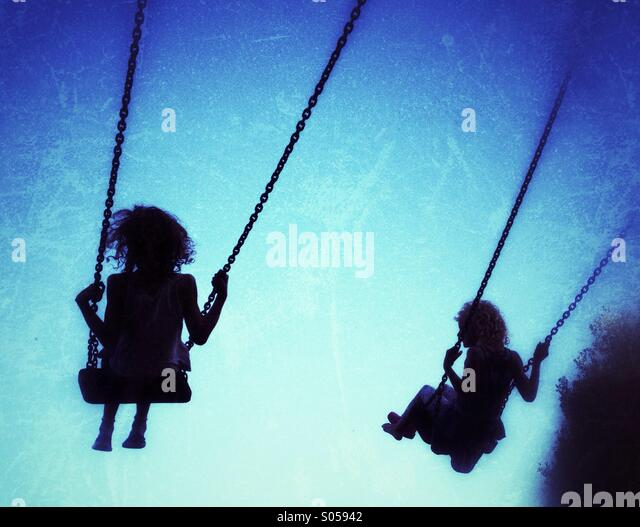 Two girls on swings silhouetted against blue sky - Stock Image