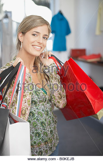 Woman in store with shopping bags smiling - Stock Image