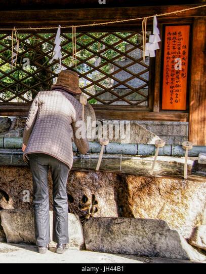 A woman using purification basin, te-mizuya, at Sumiyoshi Shrine. Osaka, Japan - Stock Image
