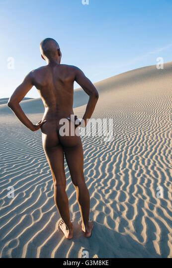 Rear view of nude woman in dessert with hands on hips - Stock Image