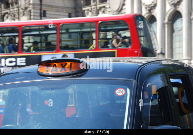 Taxi and bus in busy London traffic, England UK. - Stock Image