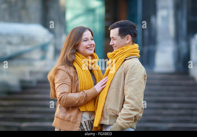 Couple of tourists taking a walk in a city street sidewalk in a sunny day - Stock Image