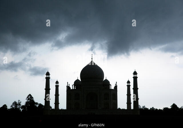 Silhouette of the Taj Mahal under storm clouds as seen from Mehtob Bagh Park across the Yamuna River in Agra, India. - Stock Image