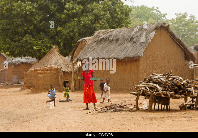 Thatched mud houses and people of Mognori Eco-Village, Ghana - Stock Image