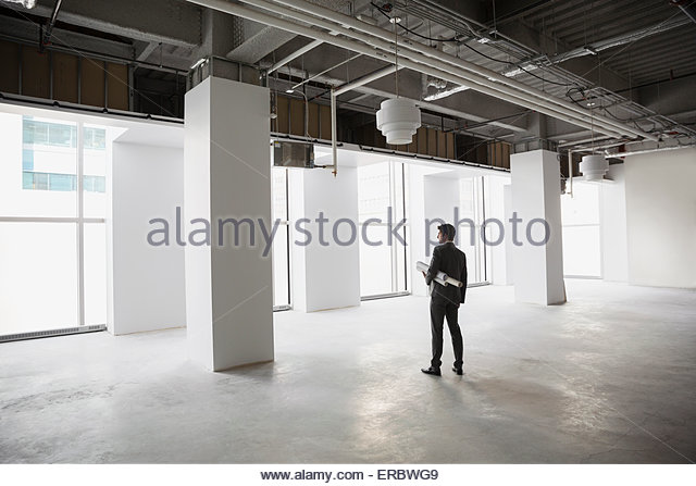 Architect with blueprints in empty office space - Stock Image