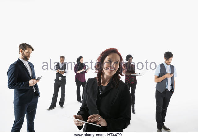 Business people using cell phones, digital tablets and laptop against white background - Stock-Bilder