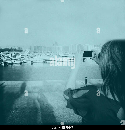 United Arab Emirates, Abu Dhabi, Woman taking photograph on phone - Stock Image