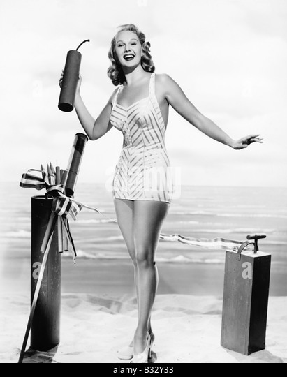 Woman in a bathing suit at the beach holding an oversized fire cracker in her hands - Stock Image
