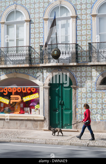 Woman walking dog past the Estonian consulate building in Tavira Algarve  Portugal Europe - Stock Image