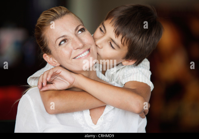 Boy kissing his mother's cheek - Stock Image