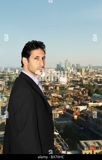 Portrait of executive with view of city landscape behind him - Stock Image