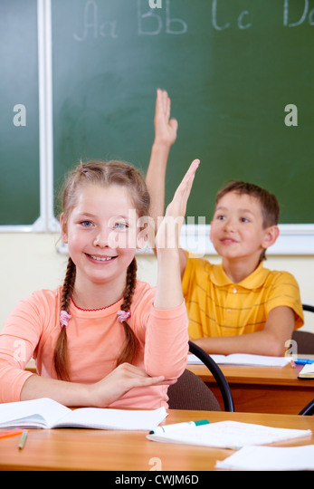 Portrait of lovely girl raising hand at workplace with schoolboy on background - Stock Image
