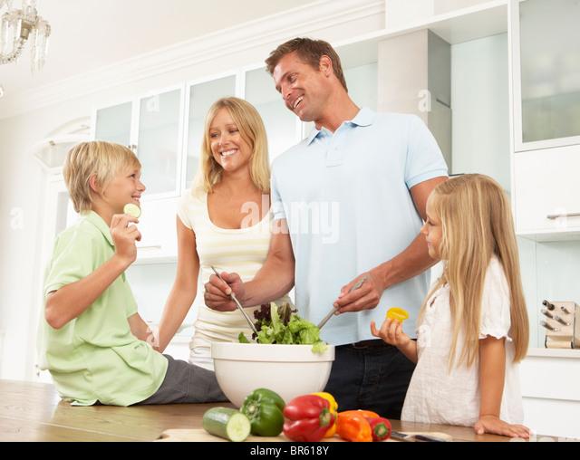 Father & Son Preparing Salad In Modern Kitchen - Stock Image