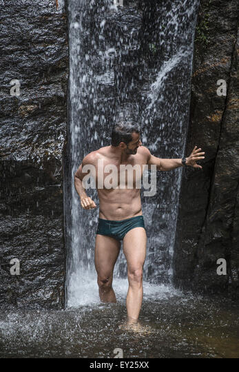 Mature man touching rock in front of waterfall in Tijuca Forest, Rio de Janeiro, Brazil - Stock Image