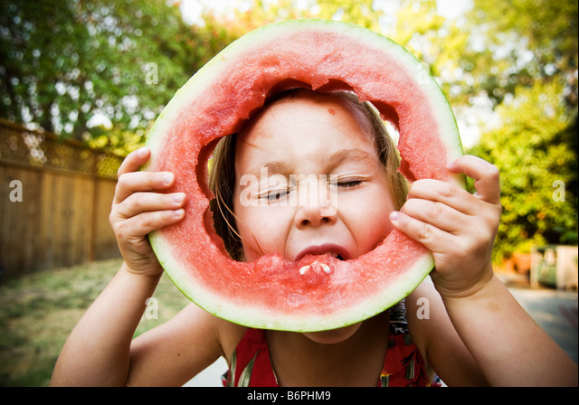 A young girl (3-5) blissfully eating a full slice of watermelon. - Stock Image