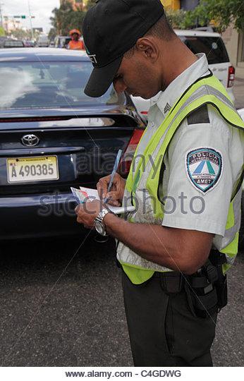 Santo Domingo Dominican Republic Avenida Mexico Hispanic man Metropolitan Police officer issue ticket citation writing - Stock Image