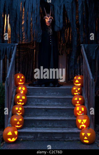 Scary lit carved pumpkins at twilight on stairs with Demon with horns on porch Haunted House on Halloween - Stock Image
