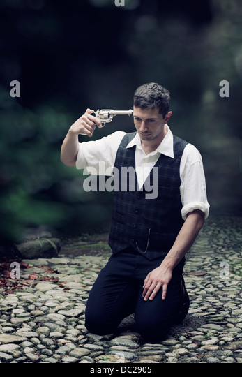 a man in vintage clothes is sitting on the ground, trying to shoot himself - Stock Image